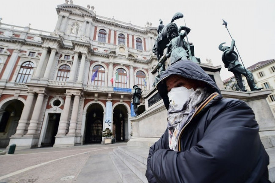 A woman wears a mask at the Carlo Alberto square, after the government decree to close cinemas, schools and urge people to work from home and not stand closer than one metre to each other, in Turin, Italy, March 05, 2020 — Reuters