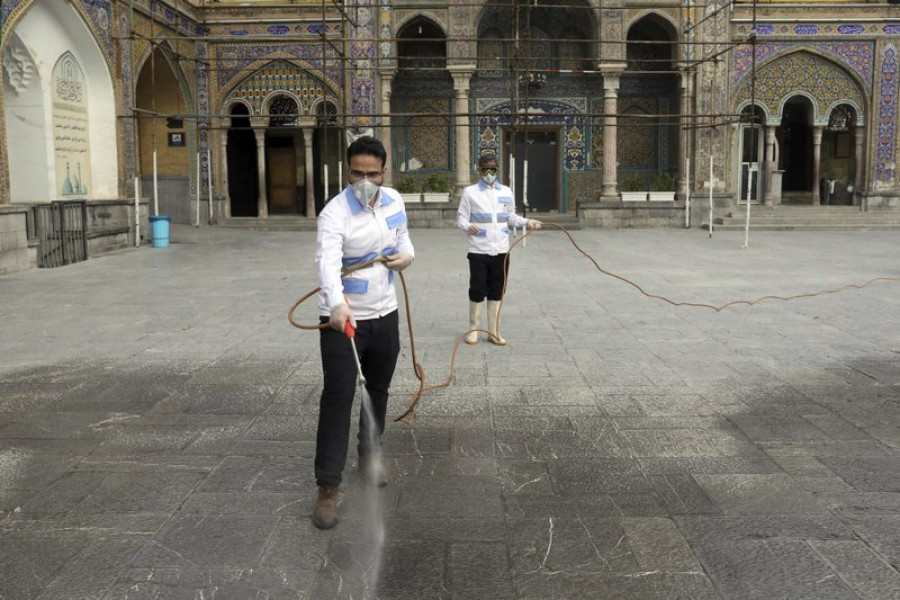 Workers disinfect the shrine of the Shiite Saint Imam Abdulazim to help prevent the spread of the new coronavirus in Shahr-e-Ray, south of Tehran, Iran, Saturday, March, 7, 2020 — AP Photo