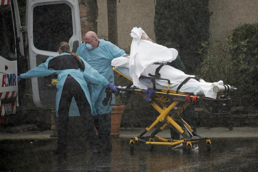 Medics transport a patient through heavy rain into an ambulance at Life Care Center of Kirkland, the long-term care facility linked to several confirmed coronavirus cases in the state, in Kirkland, Washington, US on March 7, 2020 — Reuters photo