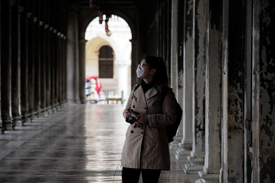 A woman wearing a protective face mask walks through St. Mark's Square after the Italian government imposed a virtual lockdown on the north of Italy including Venice to try to contain a coronavirus outbreak, in Venice, Italy, March 09, 2020 — Reuters