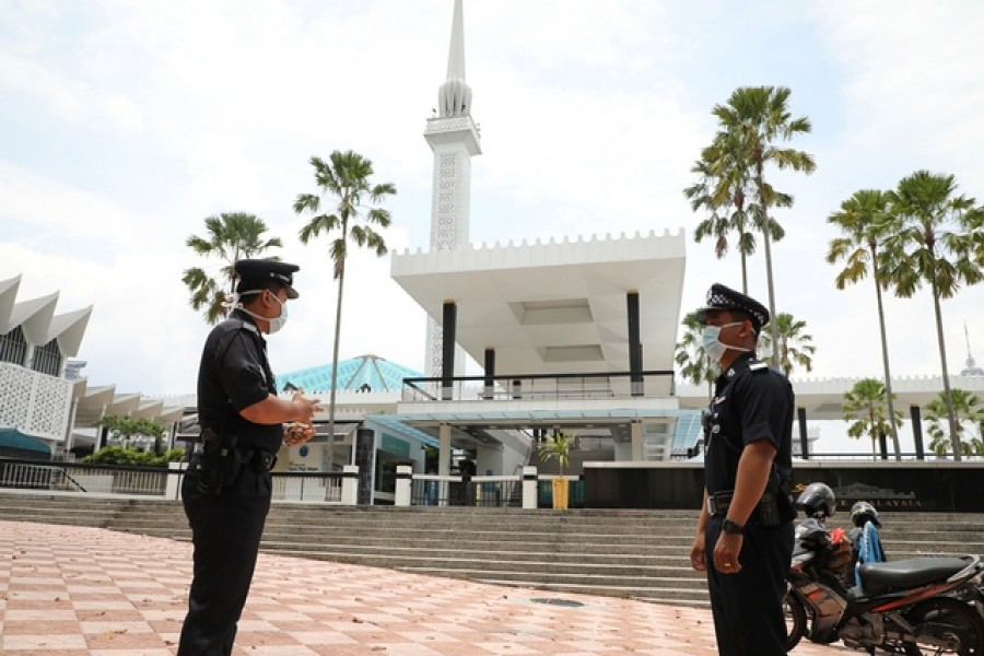 Police officers wearing protective masks stand guard outside National Mosque, after all mosques in the country suspended Friday prayers during the movement control order due to the spread of the coronavirus disease (COVID-19), in Kuala Lumpur, Malaysia Mar 20, 2020. REUTERS