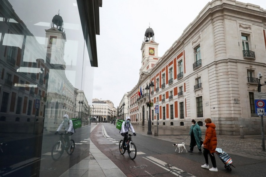 People wearing protective face masks are seen in an almost empty Puerta del Sol during a partial lockdown, which is a part of a 15-day state of emergency to combat the coronavirus disease (COVID-19) outbreak in Madrid, Spain, March 21, 2020. — Reuters