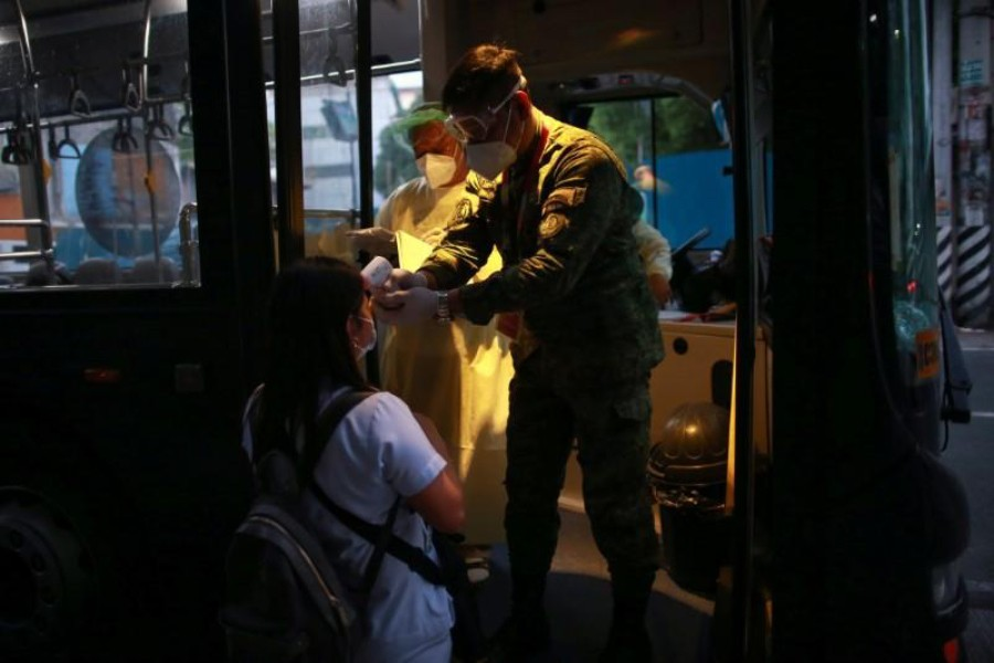 A soldier checks the body temperature of a health worker before entering a free shuttle service following the suspension of mass transportation to contain the spread of coronavirus disease (COVID-19), in Quezon City, Metro Manila, Philippines on March 20, 2020 — Reuters photo