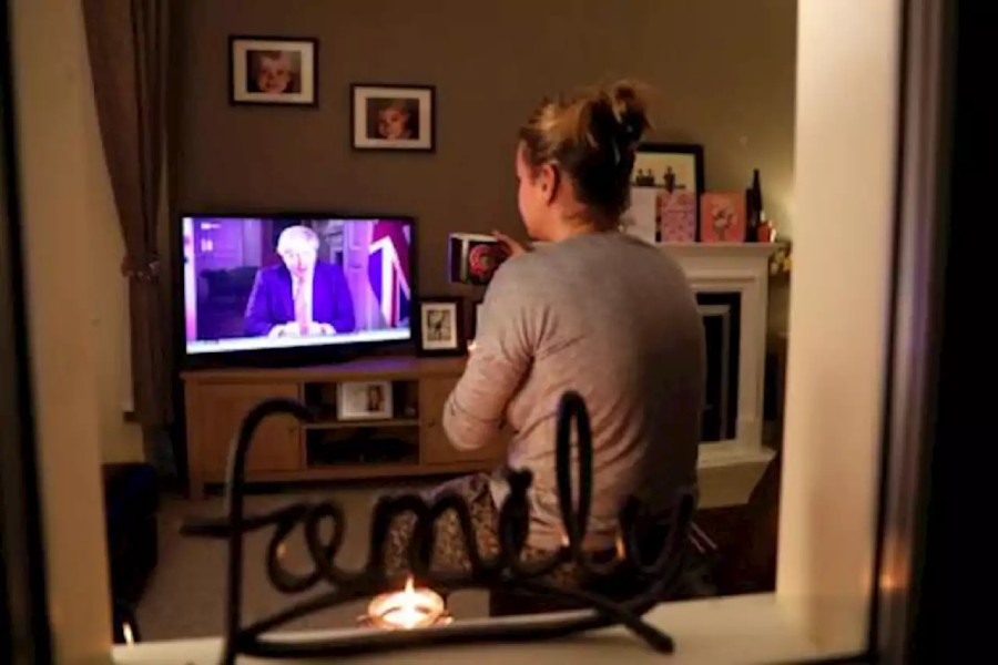 A woman watches British Prime Minister Boris Johnson's press conference as the spread of coronavirus disease (COVID-19) continues in Ouston, Britain on March 23, 2020 — Reuters photo