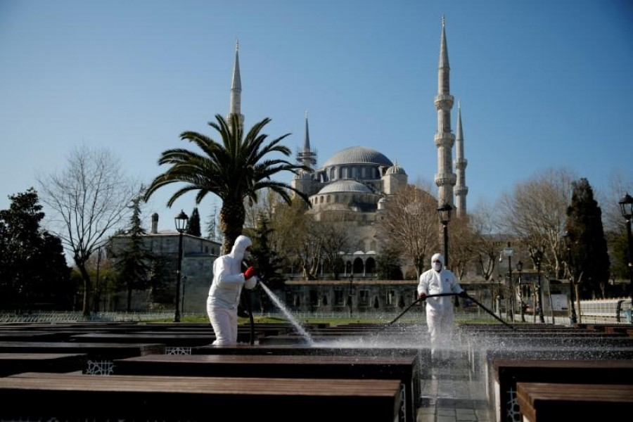 Workers in protective suits disinfect the park in front of the Blue Mosque in response to the spread of coronavirus disease (COVID-19) in Istanbul,Turkey March 21, 2020. REUTERS/Kemal Aslan