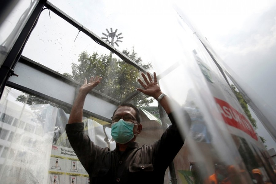 A man wearing face mask is sprayed inside a disinfection chamber, outside a shopping mall after Indonesia's capital begins a two-week emergency period to prevent the spread of coronavirus disease (COVID-19) in Jakarta, Indonesia, Mar 24, 2020. REUTERS
