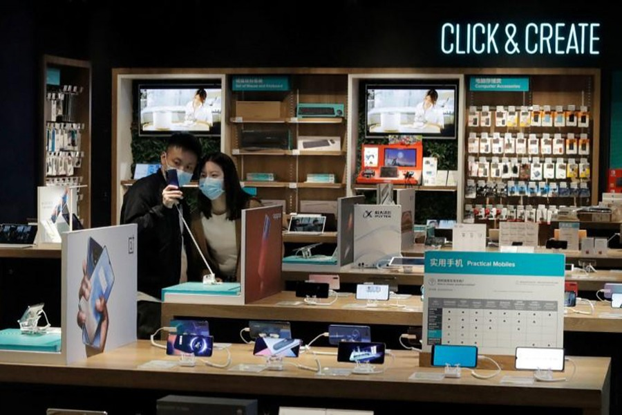 People wearing protective masks look at phones at an electronic retailer in Beijing, China on March 25, 2020 — Reuters photo