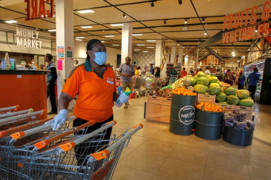 FILE PHOTO: A worker disinfects shopping trolleys as customers shop in the Naivas Supermarket, to stock their homes amid concerns about the spread of coronavirus disease (COVID-19) in Nairobi, Kenya March 23, 2020. REUTERS/Njeri Mwangi/File Photo