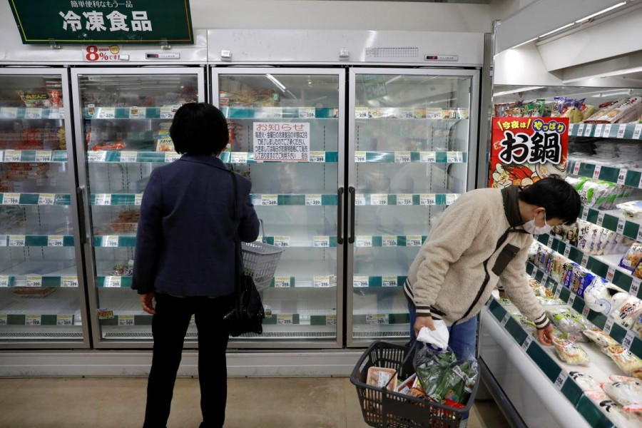 A shopper wearing a protective face mask, following an outbreak of the coronavirus disease (COVID-19), is seen next to an empty shelves of frozen foods at a supermarket in Tokyo, Japan March 27, 2020. REUTERS/Issei Kato