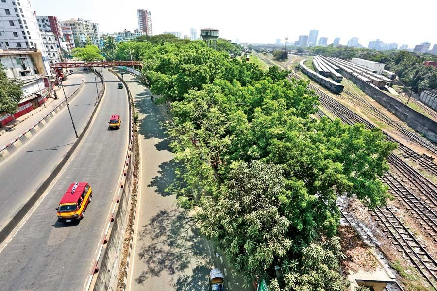 The Khilgaon flyover (left) in the city gives a desolate look while trains (right) stand idle on the railway tracks at the Kamalapur Railway Station on Friday amid the coronavirus scare — FE photo by KAZ Sumon