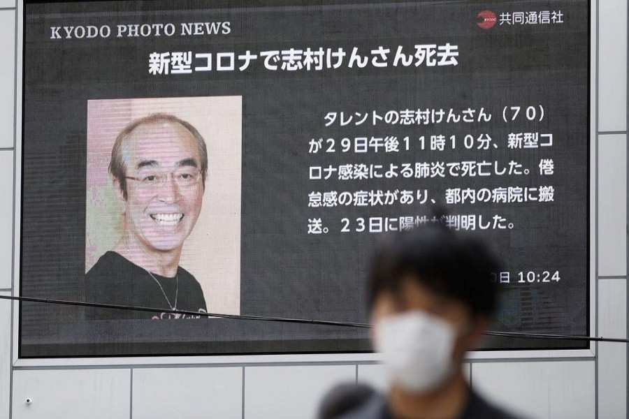 A man wearing a protective face mask, following an outbreak of the coronavirus disease (COVID-19), walks past in front of a huge screen reporting death of Japanese comedian Ken Shimura, who had been hospitalised after being infected with the new coronavirus, in Osaka, western Japan, March 30, 2020, in this photo taken by Kyodo. — Mandatory credit Kyodo/via Reuters