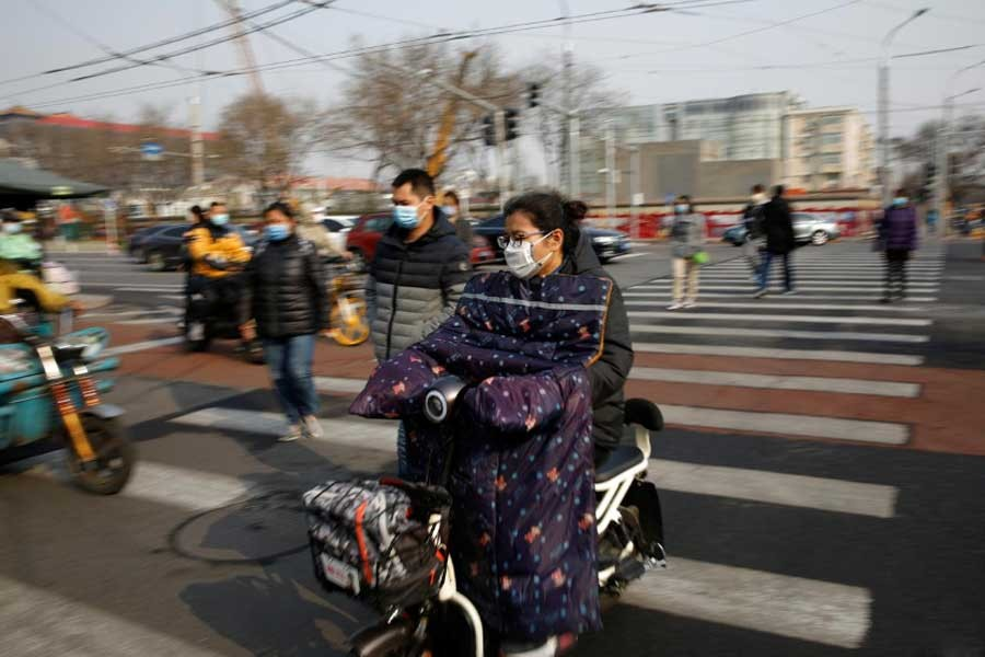 People wearing face masks riding their scooters and walk on a street following an outbreak of the coronavirus disease, in Beijing of China on Monday. –Reuters Photo