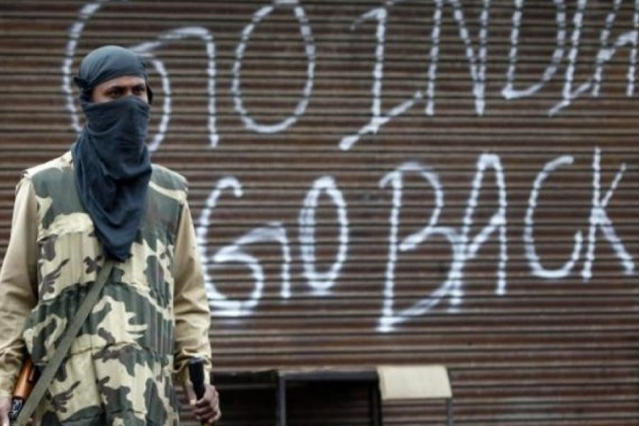An Indian police officer stands guard near a closed shop during a curfew in Srinagar — Reuters/Files