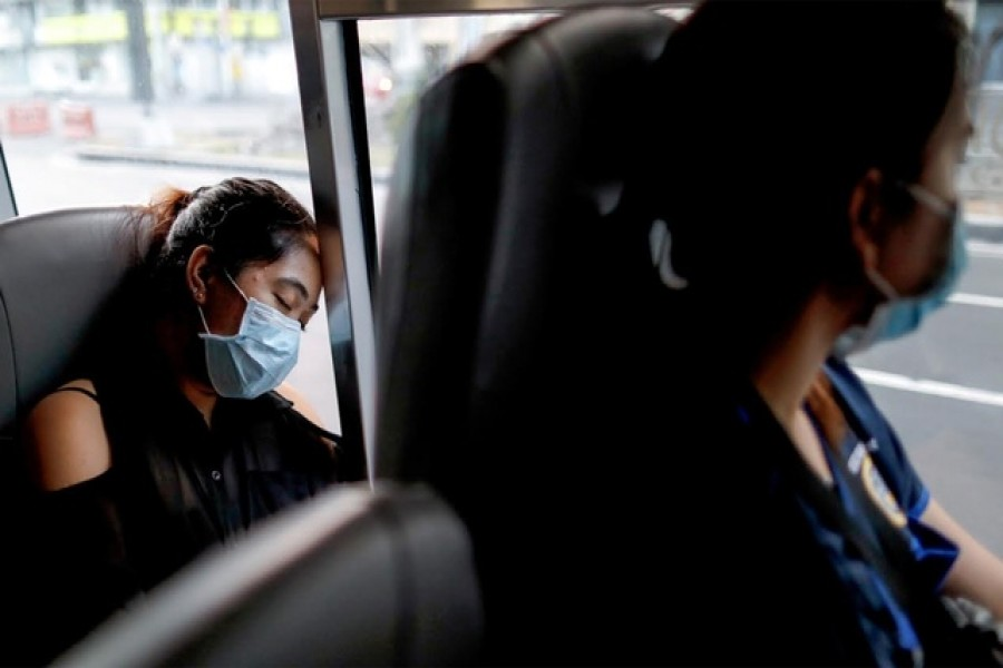 A medical worker wearing a protective mask sleeps inside a free shuttle service for healthcare workers following the suspension of mass transportation in Metro Manila to contain the spread of coronavirus disease (COVID-19), in Manila, Philippines, Mar 30, 2020. REUTERS