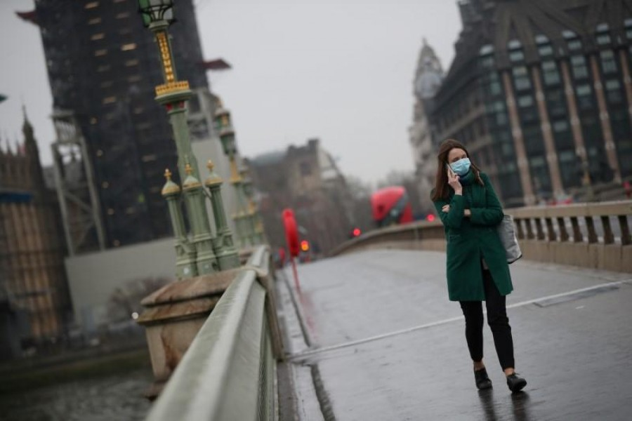 FILE PHOTO: A woman on Westminster bridge wearing a protective face mask as the spread of the coronavirus disease (COVID-19) continues, in London, Britain, March 19, 2020. REUTERS/Hannah McKay/File Photo