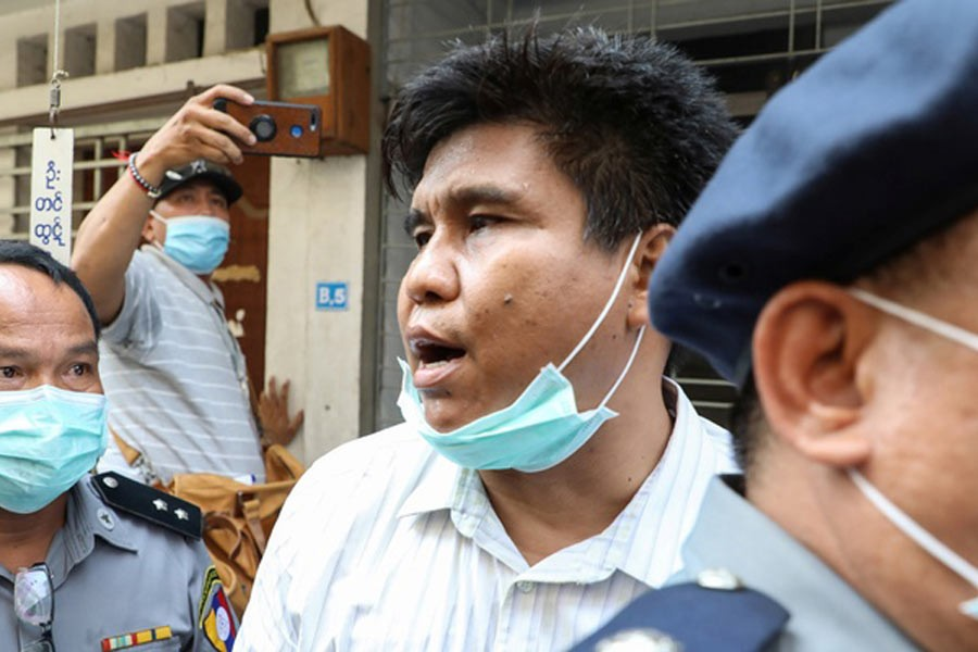 Nay Myo Lin, the editor-in-chief of Voice of Myanmar, is escorted by the police to court in Mandalay, Myanmar on Tuesday. –Reuters Photo