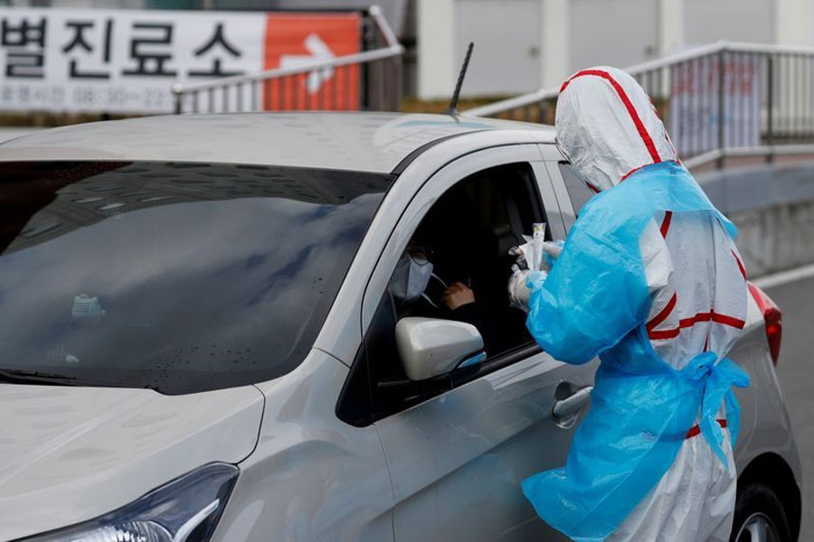 A medical staff preparing to take samples from a visitor at a 'drive-thru' testing center for the novel coronavirus disease of COVID-19 in Yeungnam University Medical Center in Daegu, South Korea last month. –Reuters File Photo