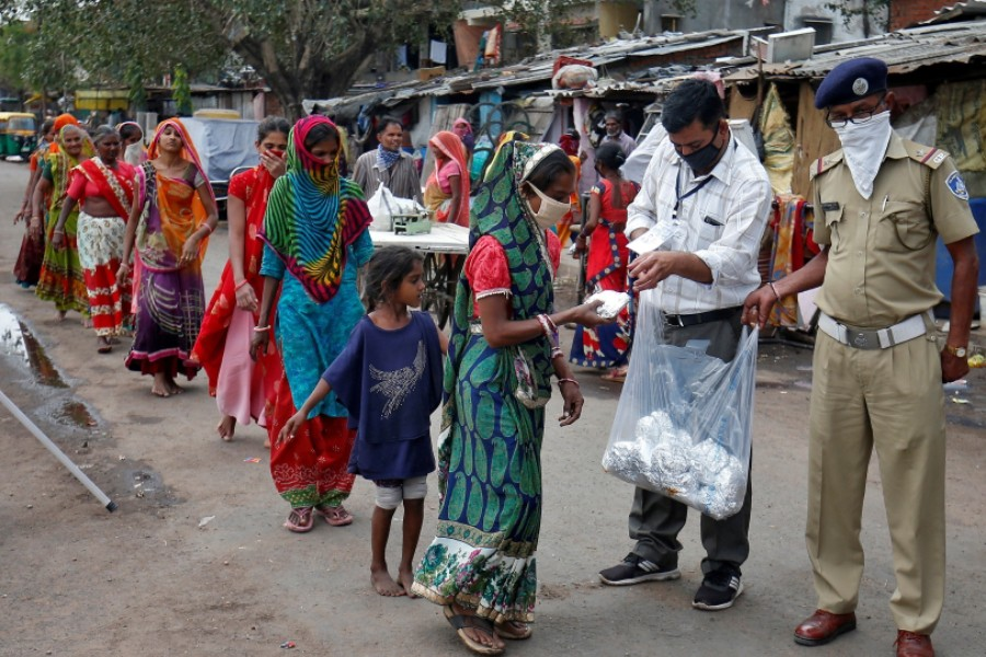 Slum dwellers in Ahmedabad receive free food packets during a 21-day nationwide lockdown - Amit Dave/Reuters