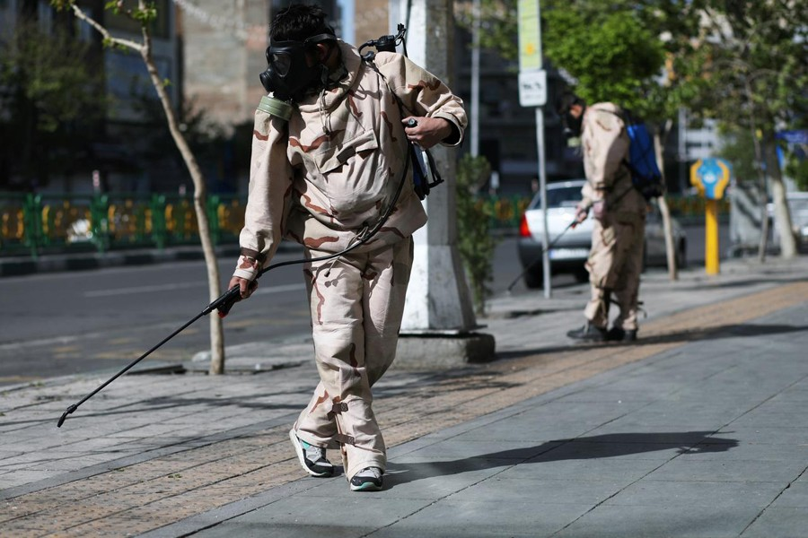 Volunteers from Basij forces wearing protective suits and face masks spray disinfectant on the streets, amid the coronavirus disease (COVID-19) fears, in Tehran, Iran on April 3, 2020 — WANA via REUTERS