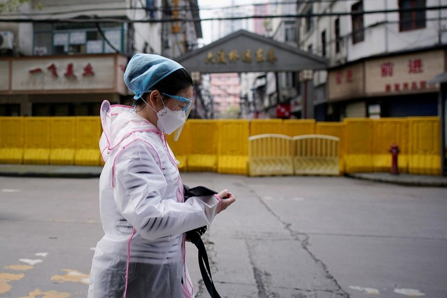 A woman wearing a face mask walks at a residential area blocked by barriers in Wuhan, Hubei province, the epicentre of China's coronavirus disease (COVID-19) outbreak, April 03, 2020. — Reuters