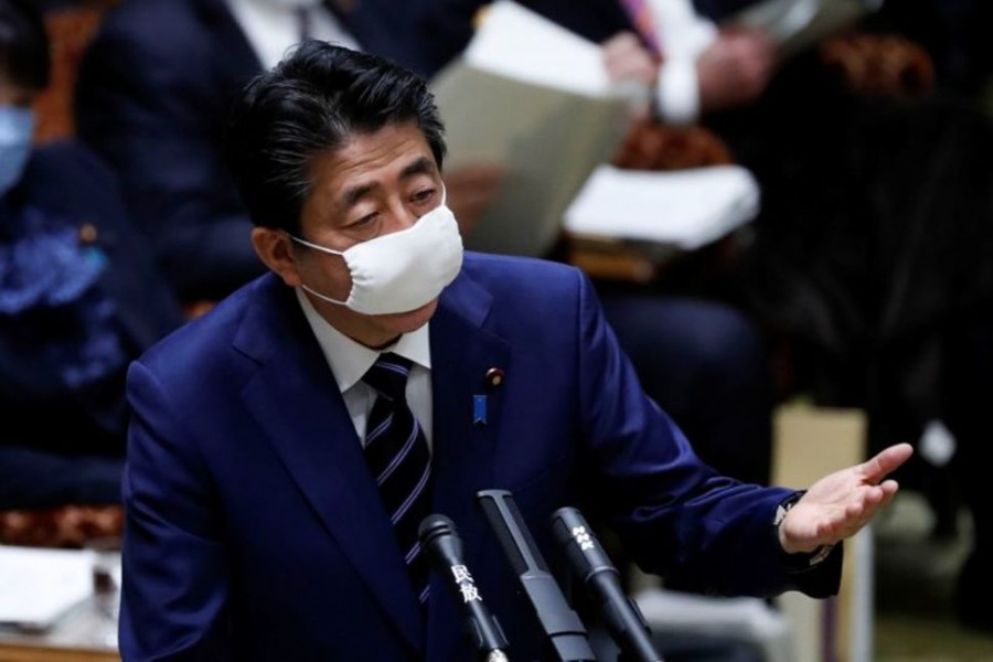 Japan's Prime Minister Shinzo Abe wears a protective face mask as he attends an upper house parliamentary session, following an outbreak of the coronavirus disease (COVID-19), in Tokyo, Japan April 1, 2020. REUTERS/Issei Kato