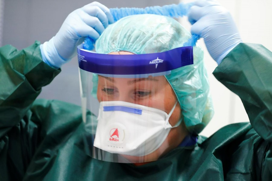 Canan Emcan, 31, chief nurse of the infection and virologist ward of Essen University Hospital puts on protection gear worn in case of coronavirus patients during a media event in Essen, Germany on March 5, 2020 — Reuters/Files