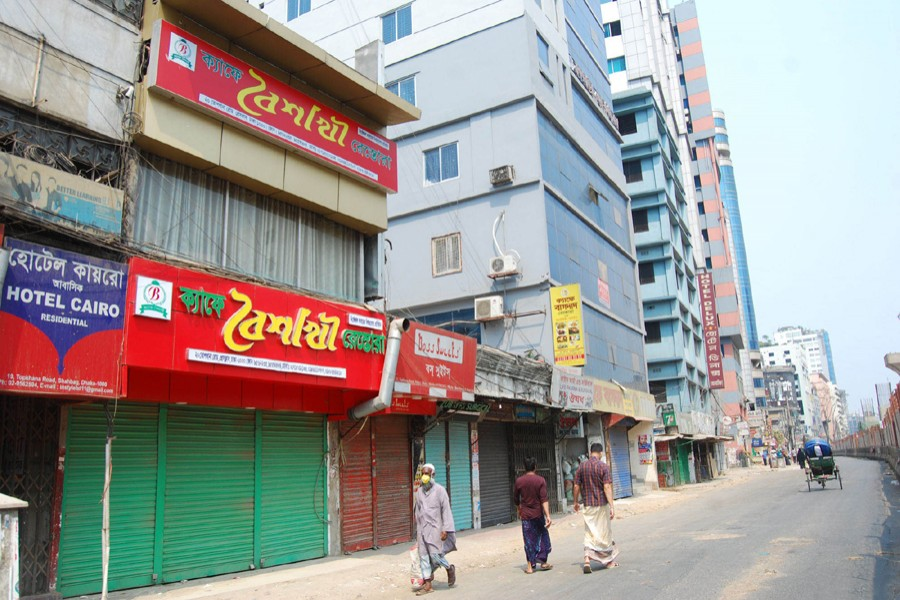 Pedestrians walk past closed shops and restaurants during a shutdown enforced by the government as a preventive measure against the coronavirus outbreak at Topkhana Road in Purana Paltan, Dhaka — Focus Bangla photo