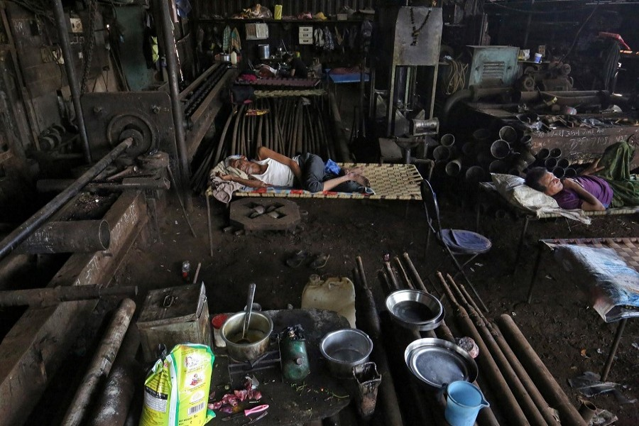 Migrants workers rest inside a workshop after it was shut due to the 21-day nationwide lockdown to slow the spread of the coronavirus disease (COVID-19), in Mumbai, India, April 07, 2020. – Reuters