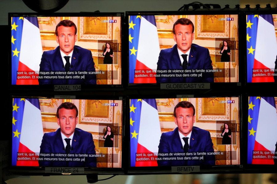 French President Emmanuel Macron is seen as he addresses the nation about the coronavirus disease (COVID-19) outbreak, on television screens in Paris, France, April 13, 2020. REUTERS/Charles Platiau