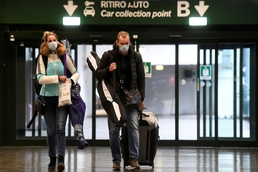 People wearing protective masks walk in Malpensa airport near Milan, Italy, March 09, 2020. — Reuters/Files
