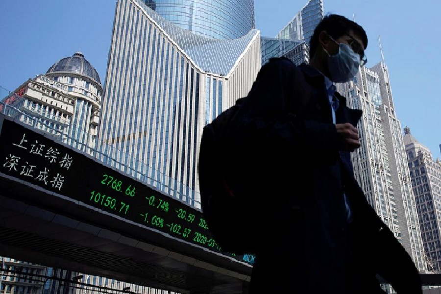 A pedestrian wearing a face mask walks near an overpass with an electronic board showing stock information, following an outbreak of the coronavirus disease (COVID-19), at Lujiazui financial district in Shanghai, China, March 17, 2020. — Reuters/Files