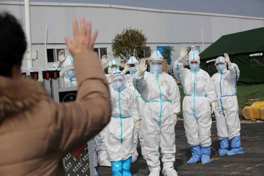 Medical personnel in protective suits wave hands to a patient who is discharged from the Leishenshan Hospital after recovering from the novel coronavirus, in Wuhan, the epicentre of the novel coronavirus outbreak, in Hubei province, China on March 1, 2020 — Reuters/Files