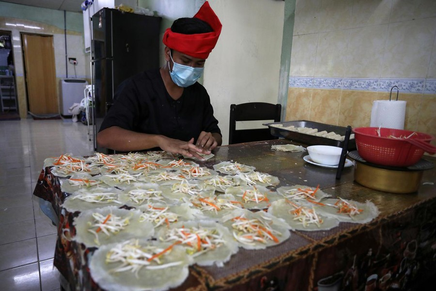 "An online Ramadan bazaar trader wraps ""Popiah"" spring rolls at his home, during the movement control order due to the outbreak of the coronavirus disease (COVID-19), in Sungai Buloh, Malaysia on April 11, 2020 — Reuters photo"
