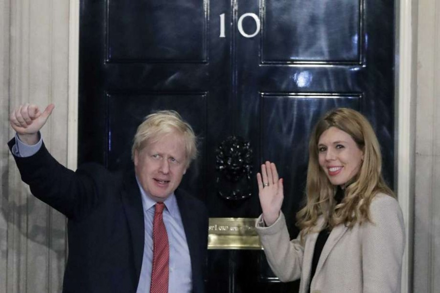 In this Friday, Dec. 13, 2019 file photo, Britain's Prime Minister Boris Johnson and his partner Carrie Symonds wave from the steps of number 10 Downing Street in London. Photo: AP