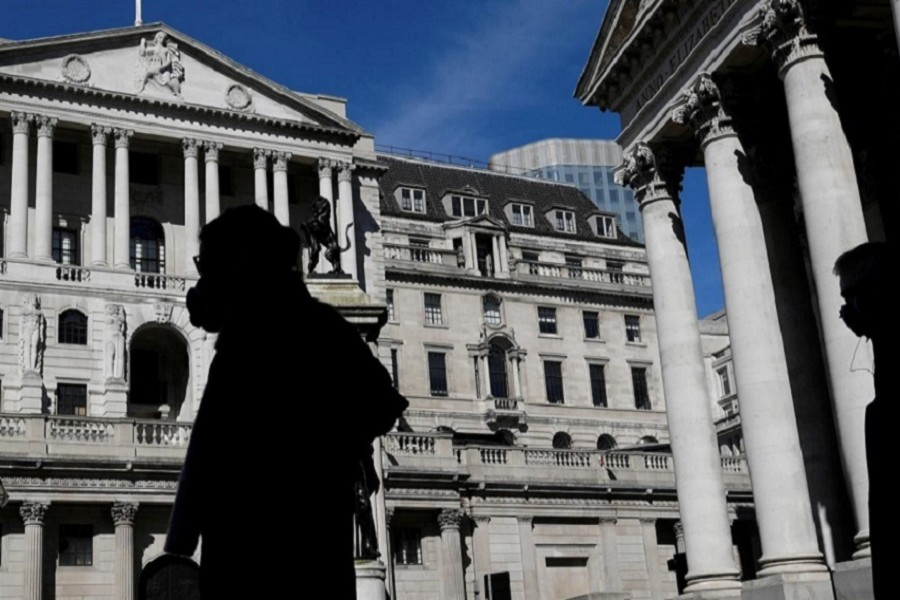 People wearing masks walk past the Bank of England, as the spread of the coronavirus disease (COVID-19) continues, in London, Britain, March 23, 2020. — Reuters/Files
