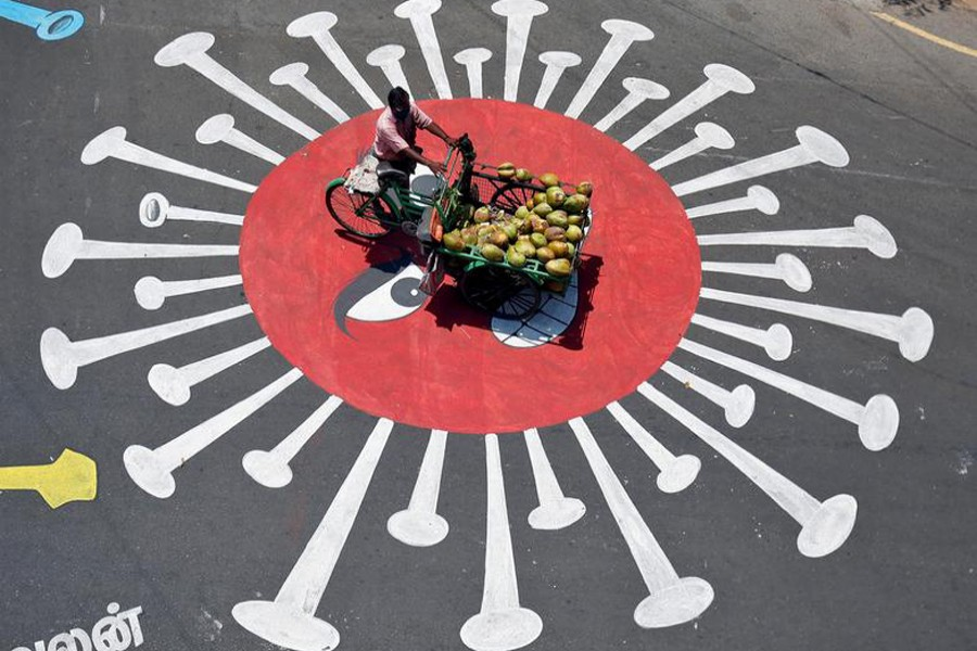 A man selling coconuts rides his trishaw on a graffiti on a road depicting the coronavirus as an attempt to raise awareness about the importance of staying at home during the nationwide lockdown to slow the spreading of the coronavirus disease (COVID-19), in Chennai, India on April 13, 2020 — Reuters/Files
