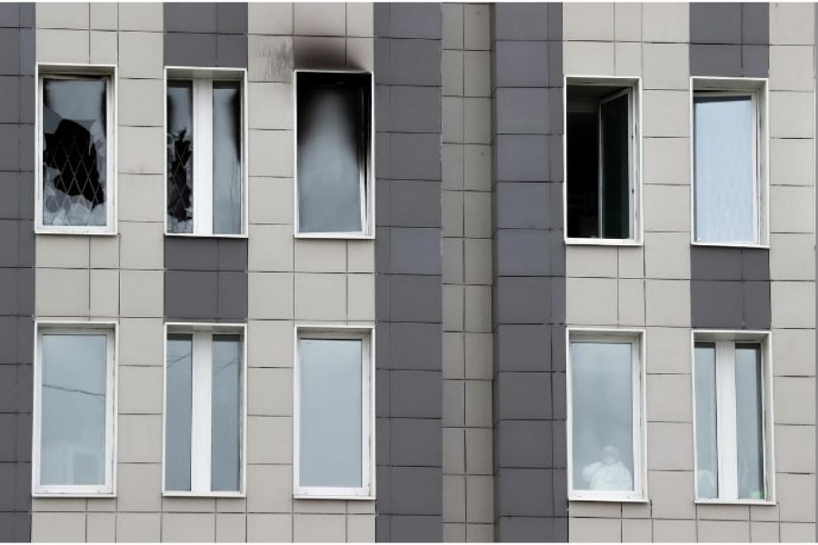 A medical specialist is seen in a window after a fire, which killed five novel coronavirus patients in an intensive care unit, at a hospital in Saint Petersburg, Russia May 12, 2020. REUTERS/Anton Vaganov