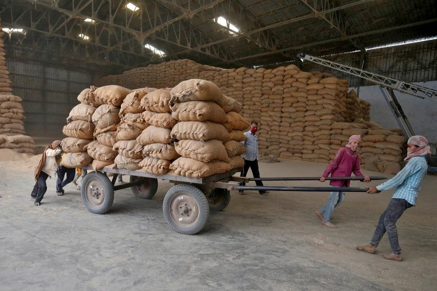 Labourers move a cart loaded with rice bags inside a food processing unit, which was reopened after weeks-long shutdown to slow the spread of coronavirus disease (COVID-19), on the outskirts of Ahmedabad, India, April 20, 2020. — Reuters/Files