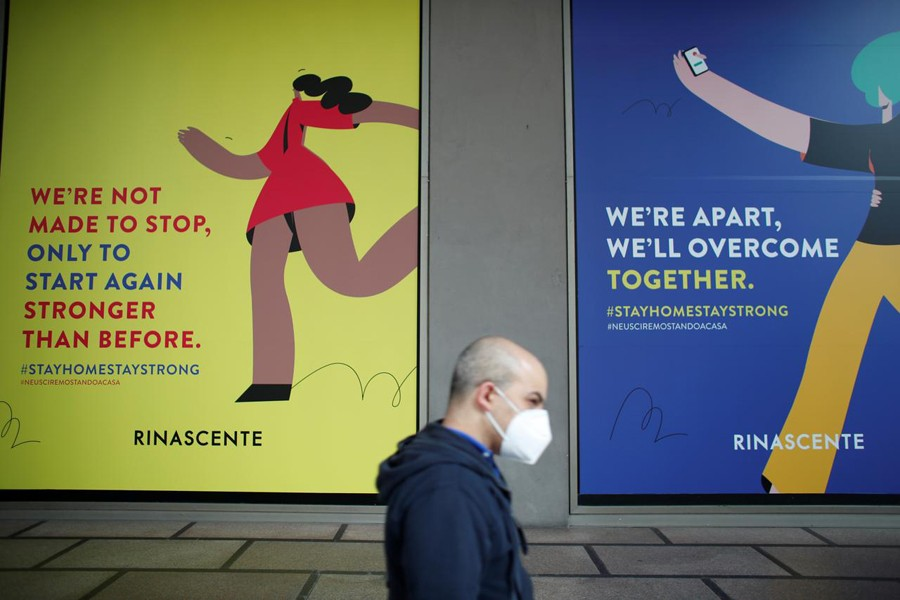 A man wearing a face mask walks past billboards of La Rinascente department store, which is due to reopen with social distancing measures applied, after it was closed because of the coronavirus outbreak in Milan, Italy on May 16, 2020 — Reuters photo