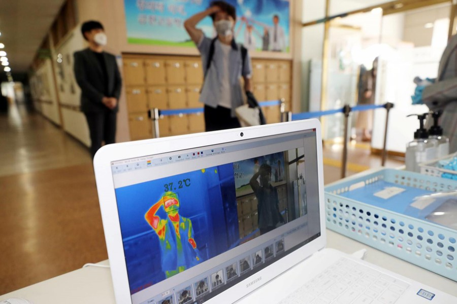 A students gets his temperature checked with a thermal imaging camera as a high school reopens, following the global outbreak of coronavirus disease (COVID-19), in Chungju, South Korea on May 20, 2020 — Yonhap via REUTERS