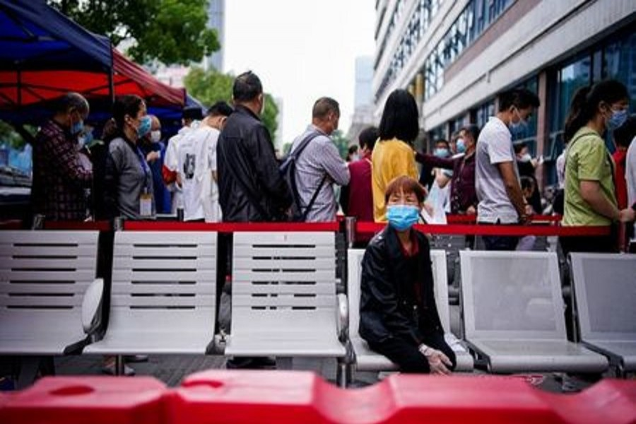 A woman wearing a face mask looks on in front of others standing in a queue for nucleic acid testings in Wuhan, the Chinese city hit hardest by the coronavirus disease, on May 16, 2020. — Reuters/Files