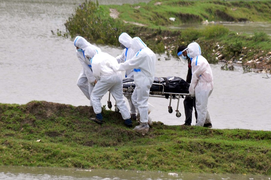 Volunteers seen carrying the corpse of a COVID-19 victim for final rituals at Sagorika area in Chattogram — Collected