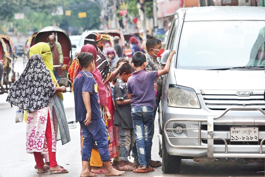 Poor people pleading for alms at Bailey Road in the city on Friday — FE photo