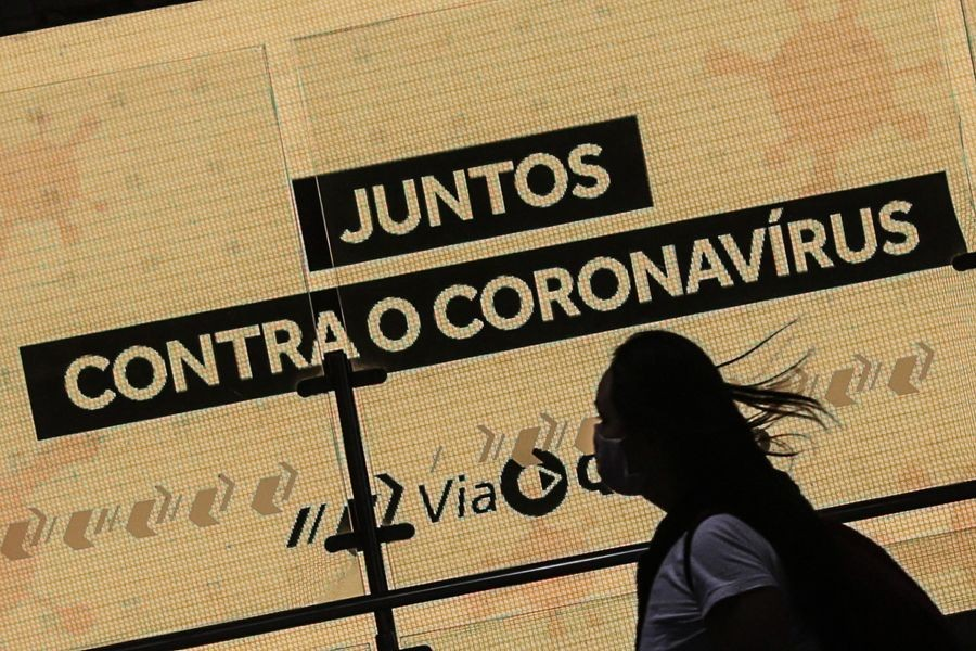 "A woman passes by a placard reading ""Together against coronavirus"" in Sao Paulo, Brazil, on May 20, 2020. (Xinhua/Rahel Patrasso)"