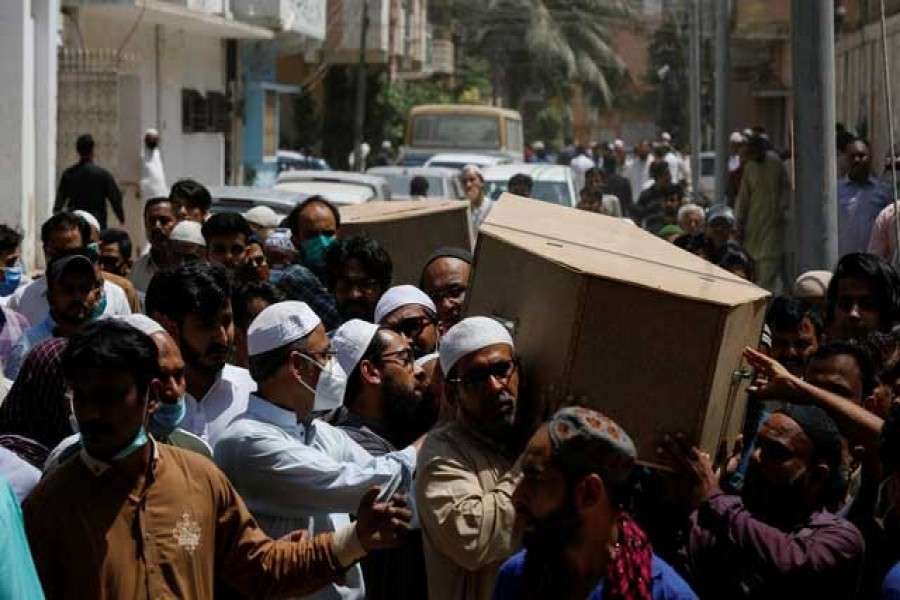 People carry the coffins of husband and wife who were killed in a plane crash, during a funeral in Karachi, Pakistan May 23, 2020. REUTERS