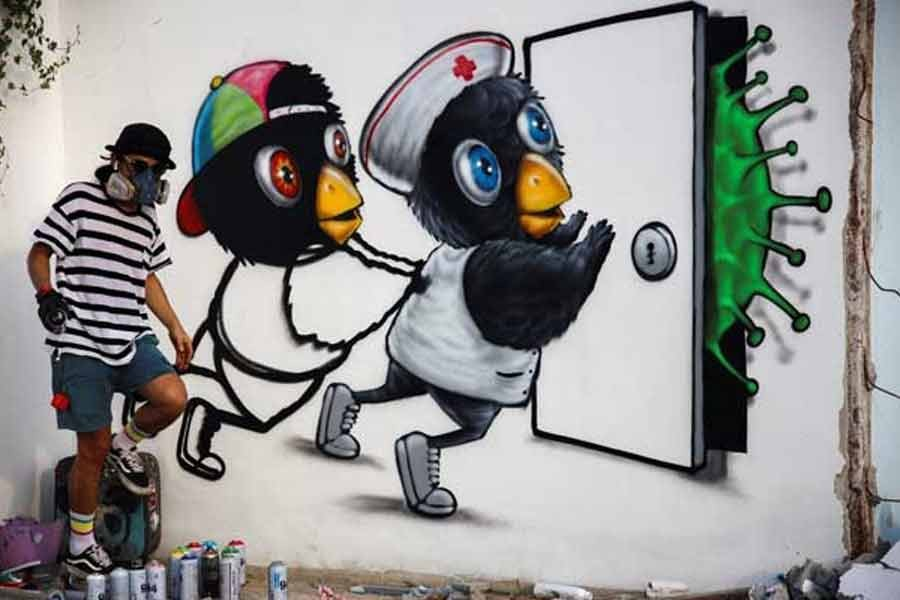 Mue Bon, a Thai street artist painting a mural depicting characters attempting to keep a virus at bay, in Bangkok, amidst an outbreak of the coronavirus disease (COVID-19) in Thailand on Thursday. –Reuters Photo