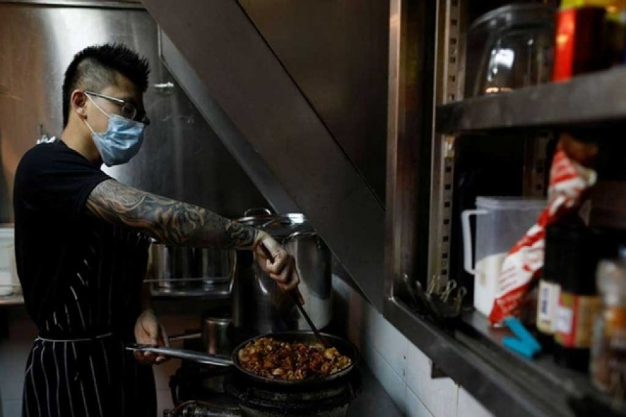 Jason Chua cooks in his stall at Hong Lim Market & Food Centre, amid the coronavirus disease outbreak in Singapore on Apr 27. REUTERS  Previous