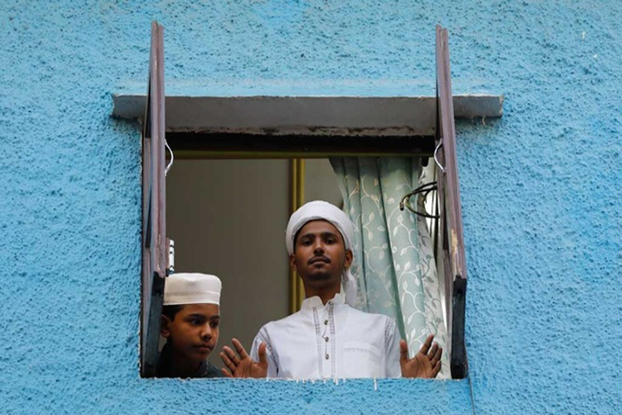 Muslim boys look out from the window of their house during Eid al-Fitr, the Muslim festival marking the end of the holy fasting month of Ramadan, amid the spread of the coronavirus disease (Covid-19), in the old quarters of Delhi, India, May 25, 2020. REUTERS