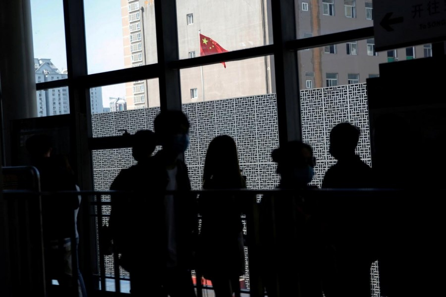 People wearing face masks to prevent the spread of the novel coronavirus disease (COVID-19) walk inside a subway station near a Chinese national flag, on the day of the opening session of the National People's Congress (NPC), in Beijing, China May 22, 2020. REUTERS/Tingshu Wang/File Photo