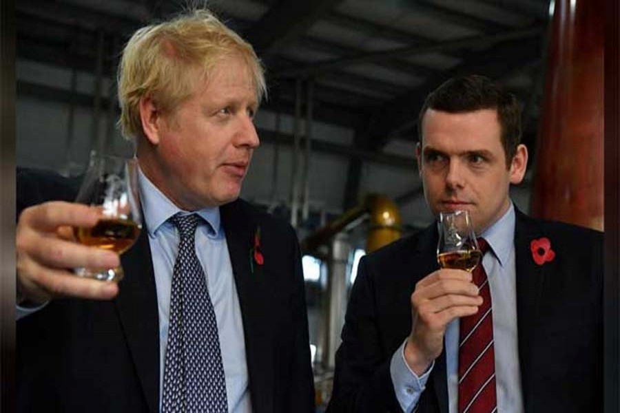 Britain's Prime Minister Boris Johnson, (L), accompanied by Conservative party candidate for Moray, Douglas Ross, tastes whisky during a general election campaign visit to Diageo's Roseisle Distillery near Elgin, Scotland, Britain Nov 7, 2019. REUTERS